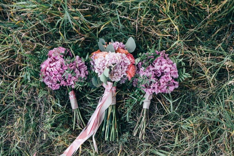 Η όμορφη γαμήλια τρία ζωηρόχρωμη ανθοδέσμη για τη νύφη και τους μάρτυρές της βρίσκεται στη χλόη στοκ εικόνα με δικαίωμα ελεύθερης χρήσης