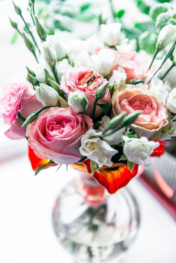 Η όμορφη γαμήλια ανθοδέσμη των ρόδινων και άσπρων τριαντάφυλλων, γαμήλια δαχτυλίδια βρίσκεται στην κορυφή στοκ φωτογραφία