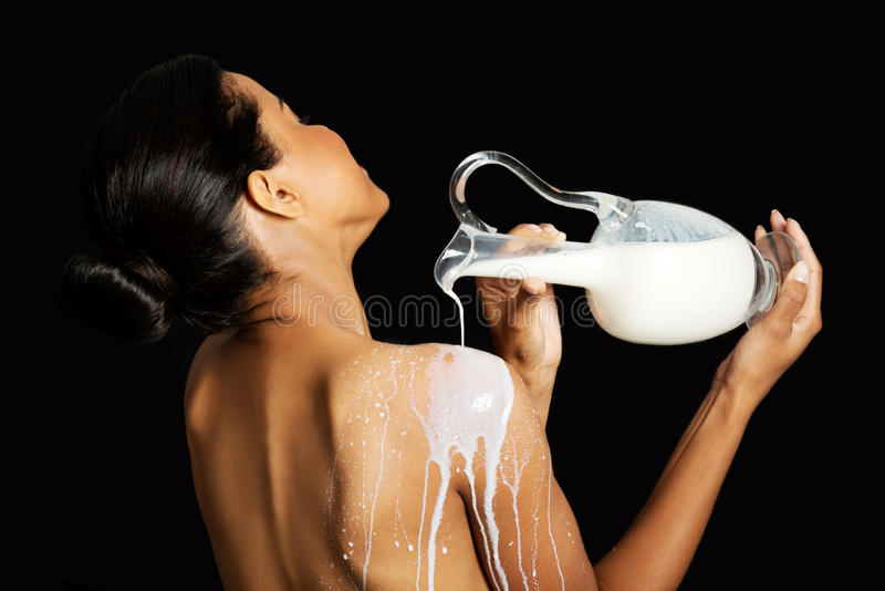 Η όμορφη γυμνή γυναίκα χύνει το γάλα σε την πίσω. στοκ εικόνες με δικαίωμα ελεύθερης χρήσης