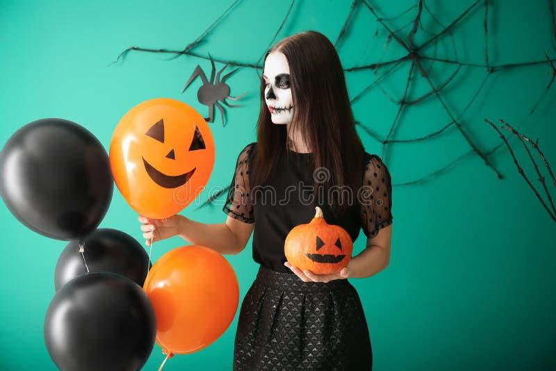 Η όμορφη γυναίκα έντυσε για αποκριές με την κολοκύθα και τα μπαλόνια που στέκονται κοντά στο διακοσμημένο τοίχο στοκ φωτογραφίες