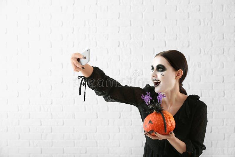 Η όμορφη γυναίκα έντυσε για αποκριές με την κολοκύθα που παίρνει selfie κοντά στον ελαφρύ τοίχο στοκ φωτογραφία με δικαίωμα ελεύθερης χρήσης