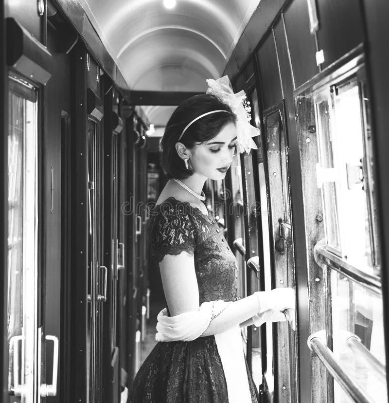 Η όμορφη γυναίκα έντυσε στο κόκκινο φόρεμα τσαγιού τσαγιού εκλεκτής ποιότητας στο κινητήριο τραίνο στοκ φωτογραφίες