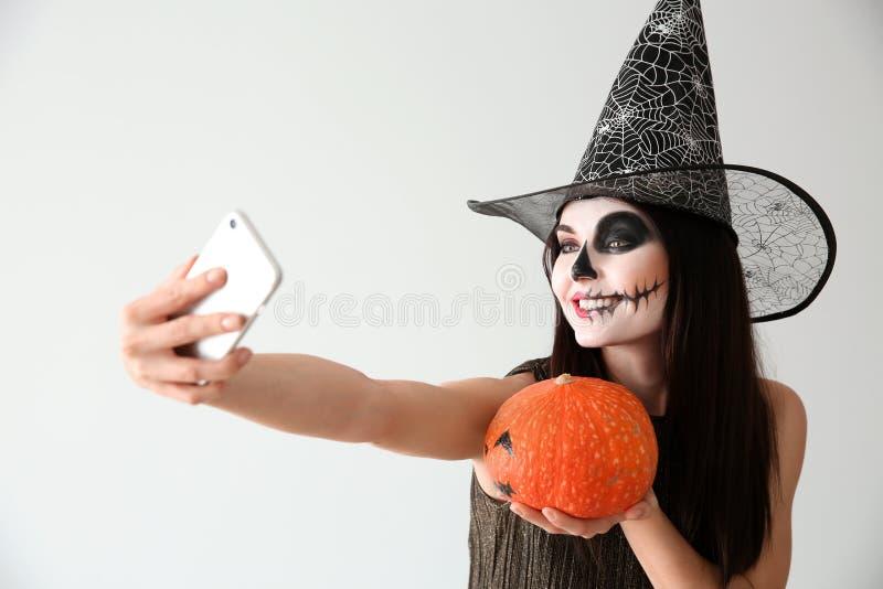 Η όμορφη γυναίκα έντυσε ως μάγισσα για αποκριές με την κολοκύθα που παίρνει selfie στο ελαφρύ υπόβαθρο στοκ εικόνα με δικαίωμα ελεύθερης χρήσης