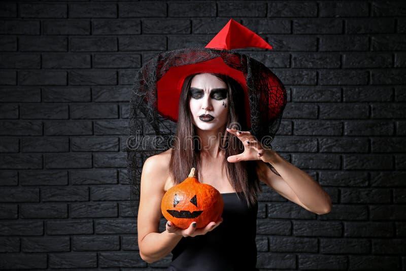 Η όμορφη γυναίκα έντυσε ως μάγισσα για αποκριές με την κολοκύθα στο σκοτεινό υπόβαθρο στοκ φωτογραφίες