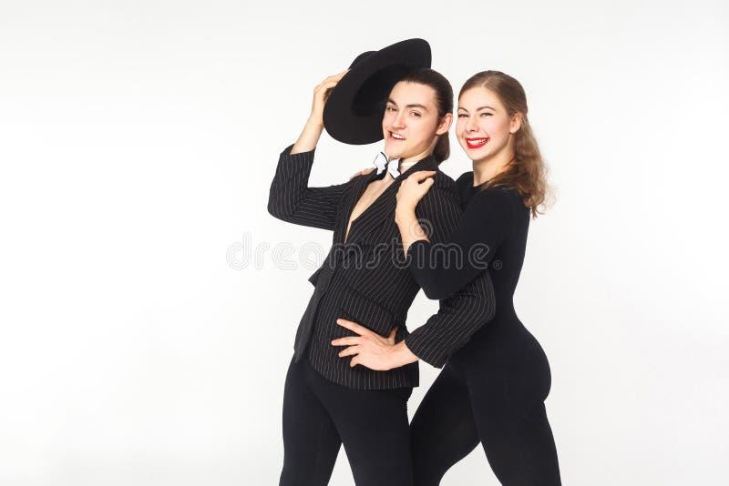 Η όμορφη γυναίκα αγκαλιάζει τον υπερήφανο άνδρα, που εξετάζει τη κάμερα στοκ εικόνα