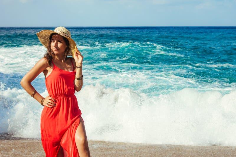 Η όμορφη γυναίκα απολαμβάνει τη θέα των κυμάτων στην παραλία Κορίτσι που χαλαρώνει και που απολαμβάνει τις διακοπές που περπατούν στοκ εικόνες