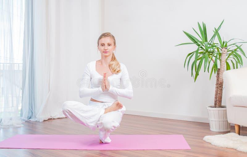 Η όμορφη γυναίκα ασκεί τη γιόγκα στο σπίτι στο χαλί γιόγκας, το κορίτσι που κάνει τη μισή ισορροπία toe Lotus θέτει στοκ εικόνες