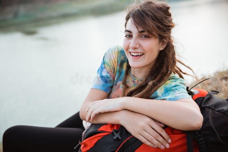 Η όμορφη γυναίκα βάζει στη χλόη απολαμβάνει το ταξίδι, κάμερα στοκ φωτογραφία
