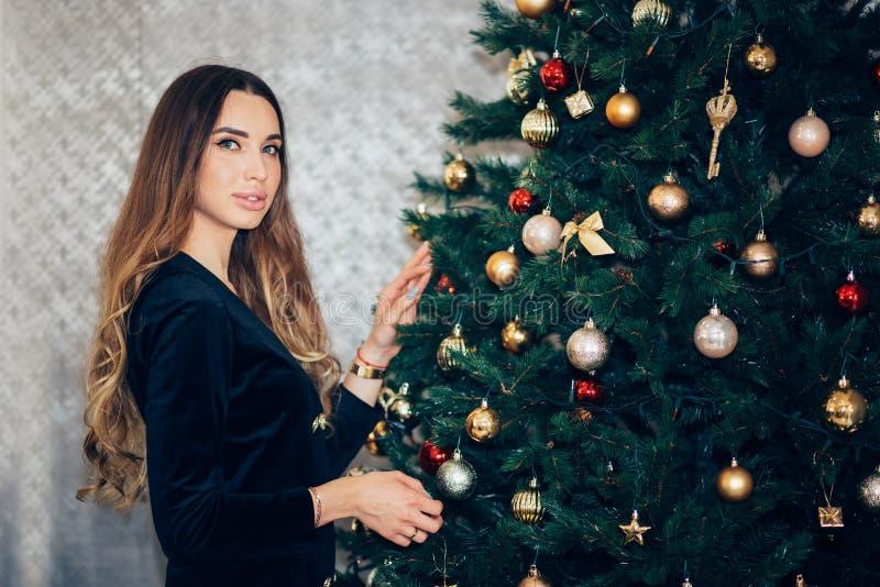 Η όμορφη γυναίκα διακοσμεί το χριστουγεννιάτικο δέντρο σε ένα εσωτερικό σπιτιών στοκ φωτογραφίες
