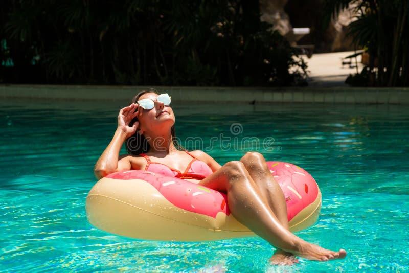 Η όμορφη γυναίκα και διογκώσιμος κολυμπά το δαχτυλίδι στη μορφή doughnut στη λίμνη στοκ εικόνες με δικαίωμα ελεύθερης χρήσης