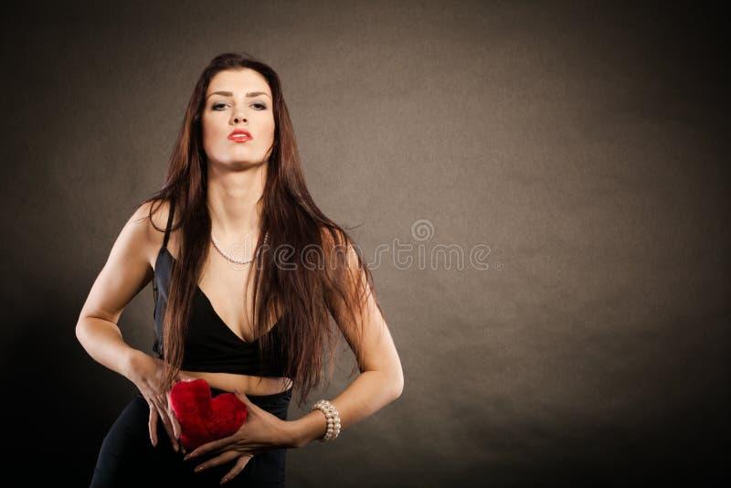 Η όμορφη γυναίκα κρατά την κόκκινη καρδιά στο Μαύρο στοκ φωτογραφία με δικαίωμα ελεύθερης χρήσης