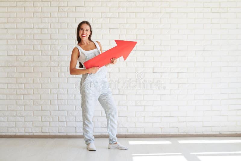 Η όμορφη γυναίκα κρατά το μεγάλο κόκκινο βέλος εγγράφου στοκ εικόνες