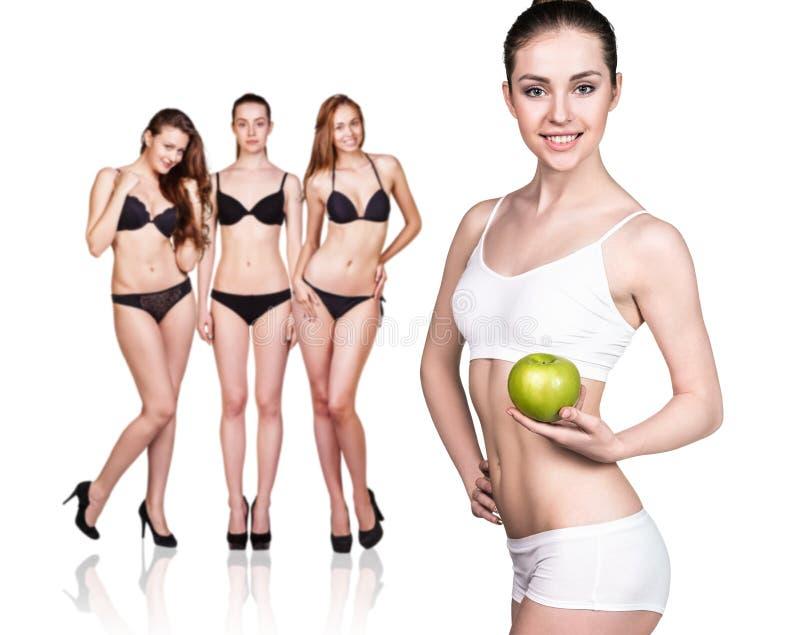 Η όμορφη γυναίκα κρατά το πράσινο μήλο στοκ φωτογραφία