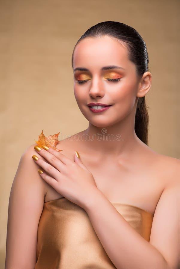 Η όμορφη γυναίκα μέσα με τα ξηρά φύλλα φθινοπώρου στοκ εικόνες με δικαίωμα ελεύθερης χρήσης