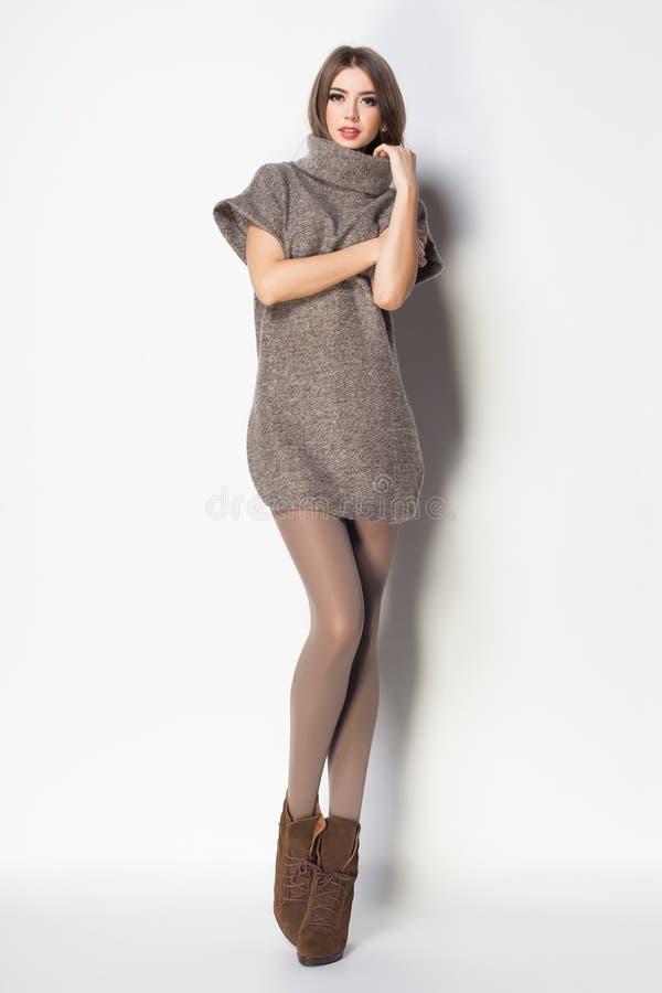 Η όμορφη γυναίκα με τα μακριά προκλητικά πόδια έντυσε την κομψή τοποθέτηση στο θόριο στοκ εικόνες