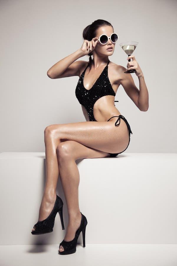Η όμορφη γυναίκα με τη γοητεία αποτελεί μοντέρνο μαύρο σε swimwear Κοκτέιλ γυαλιού ποτών στοκ φωτογραφία με δικαίωμα ελεύθερης χρήσης