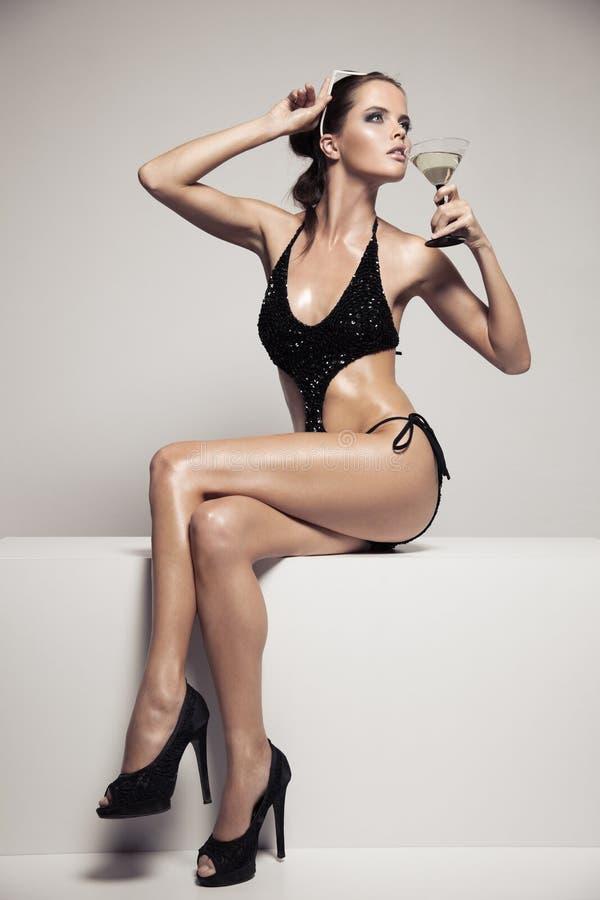 Η όμορφη γυναίκα με τη γοητεία αποτελεί μοντέρνο μαύρο σε swimwear Κοκτέιλ γυαλιού ποτών στοκ εικόνες με δικαίωμα ελεύθερης χρήσης