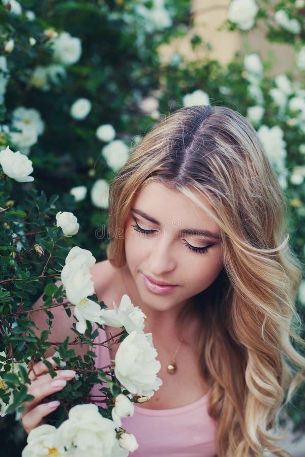 Η όμορφη γυναίκα με τη μακριά σγουρή τρίχα μυρίζει τα άσπρα τριαντάφυλλα υπαίθρια, πορτρέτο κινηματογραφήσεων σε πρώτο πλάνο του  στοκ φωτογραφίες