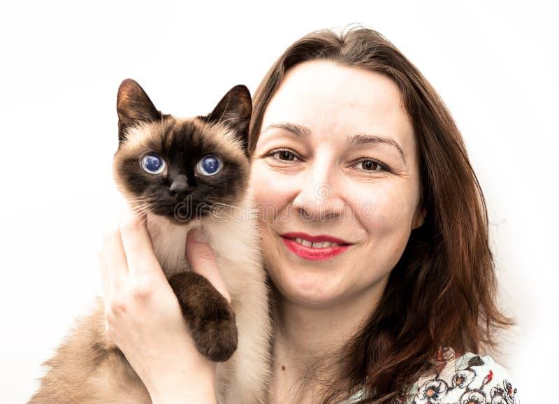 Η όμορφη γυναίκα με τη σιαμέζα γάτα στα όπλα της χαμογελά στο ασβέστιο στοκ φωτογραφίες με δικαίωμα ελεύθερης χρήσης