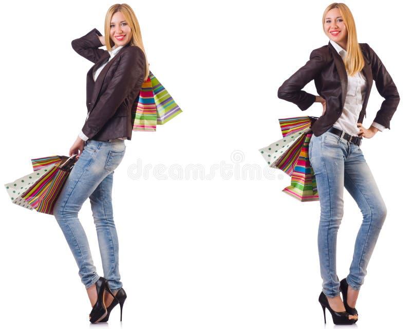 Η όμορφη γυναίκα με τις τσάντες αγορών που απομονώνεται στο λευκό στοκ φωτογραφία
