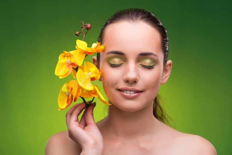 Η όμορφη γυναίκα με το κίτρινο λουλούδι ορχιδεών στοκ φωτογραφία