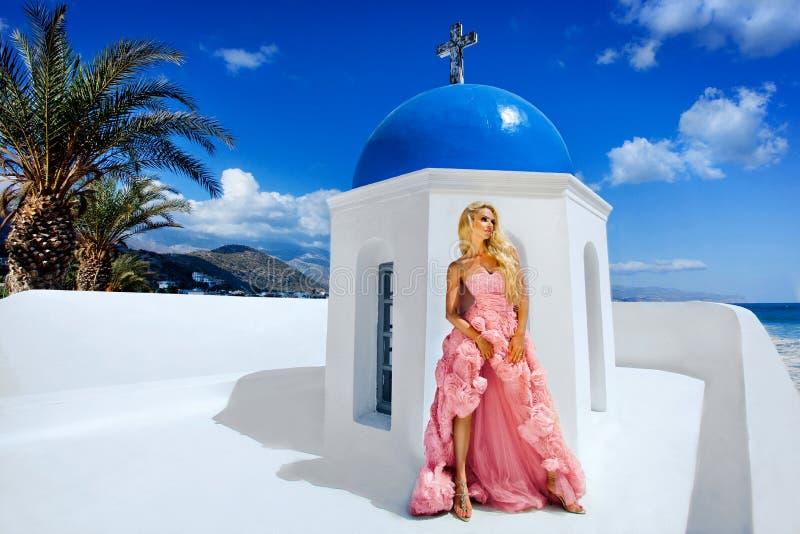Η όμορφη γυναίκα, νύφη σε ένα κομψό γαμήλιο φόρεμα, στέκεται στα πλαίσια ενός νησιού Santorini πολυτέλειας στοκ φωτογραφία