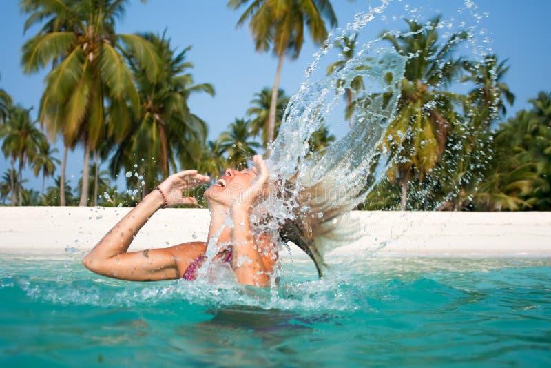 Η όμορφη γυναίκα ξαναρίχνει το τρίχωμα από το ύδωρ στοκ εικόνα