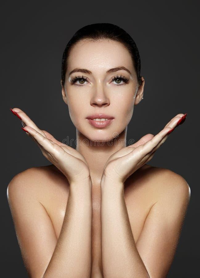 Η όμορφη γυναίκα παρουσιάζει πρόσωπο erfect της με τη σύνθεση μόδας Ακραία eyelashes, παχουλά χείλια, καθαρό δέρμα Fresh spa κοιτ στοκ φωτογραφία
