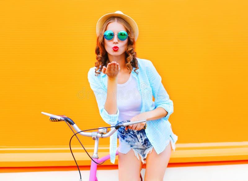 Η όμορφη γυναίκα πορτρέτου στέλνει ένα φιλί αέρα κοντά στο ποδήλατο στοκ εικόνες