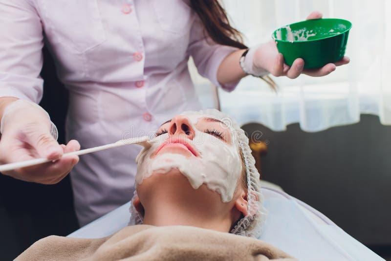 Η όμορφη γυναίκα που έχει ένα του προσώπου καλλυντικό τρίβει την επεξεργασία από τον επαγγελματικό δερματολόγο wellness spa Αντι- στοκ εικόνες
