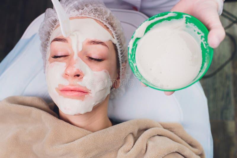 Η όμορφη γυναίκα που έχει ένα του προσώπου καλλυντικό τρίβει την επεξεργασία από τον επαγγελματικό δερματολόγο wellness spa Αντι- στοκ εικόνες με δικαίωμα ελεύθερης χρήσης