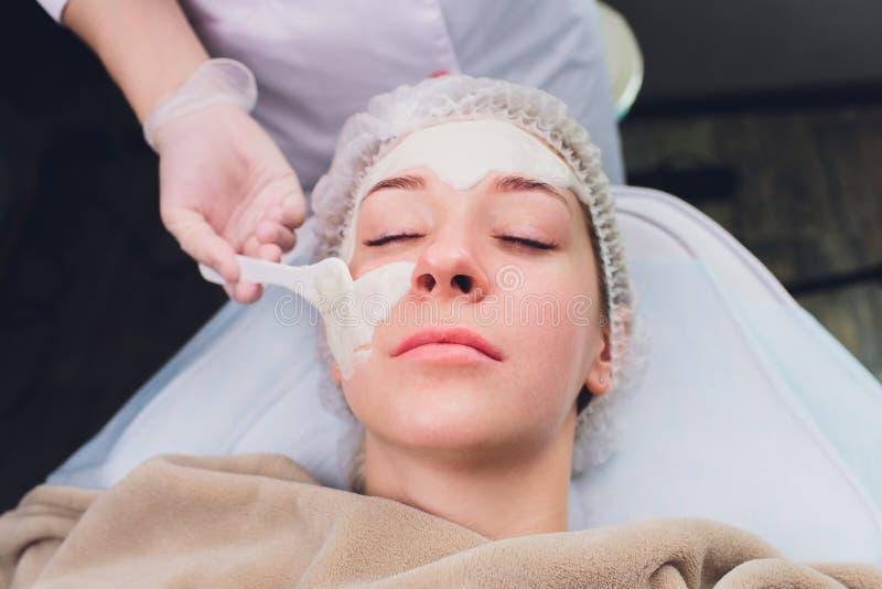 Η όμορφη γυναίκα που έχει ένα του προσώπου καλλυντικό τρίβει την επεξεργασία από τον επαγγελματικό δερματολόγο wellness spa Αντι- στοκ εικόνα