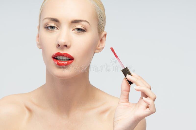 Η όμορφη γυναίκα που εφαρμόζει το χείλι σχολιάζει στοκ φωτογραφίες με δικαίωμα ελεύθερης χρήσης