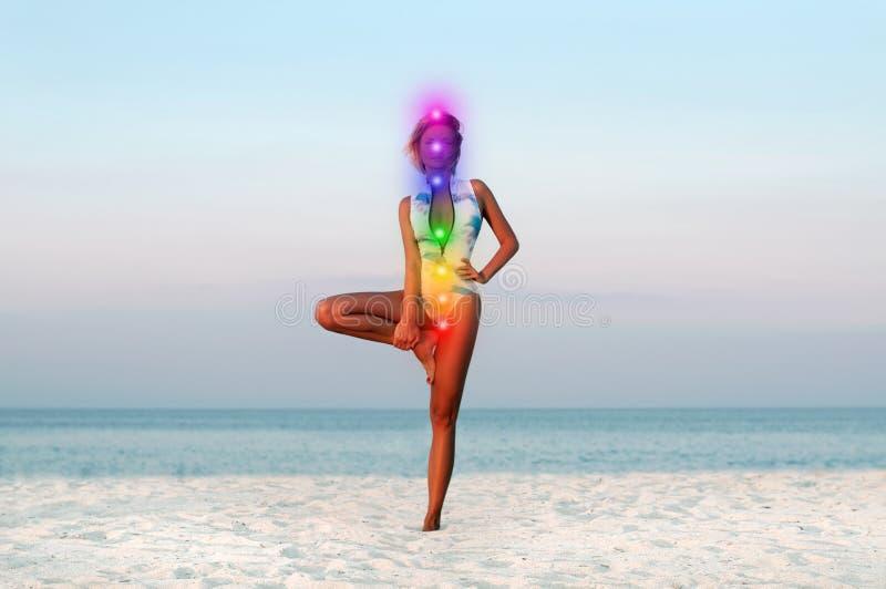 Η όμορφη γυναίκα που κάνει το δέντρο γιόγκας θέτει στην παραλία στοκ εικόνα