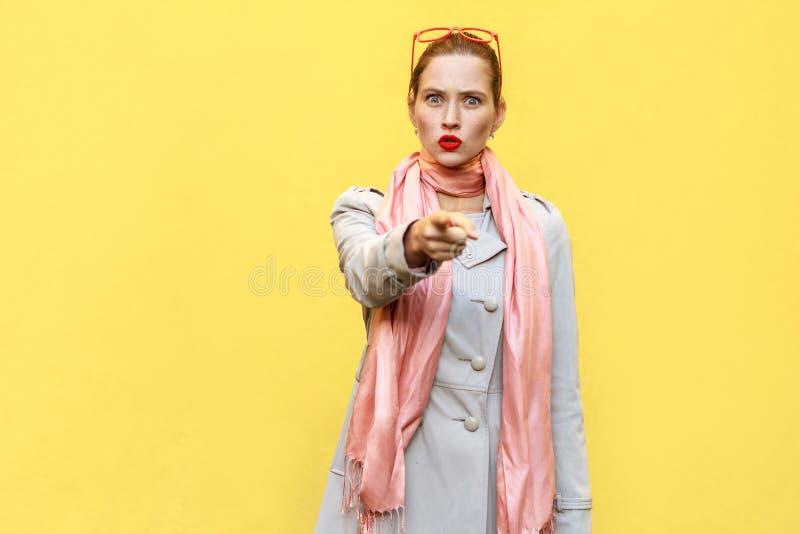 Η όμορφη γυναίκα, που φορά το παλτό φθινοπώρου, ανοίγοντας τα στόματα ευρέως, στοκ φωτογραφία