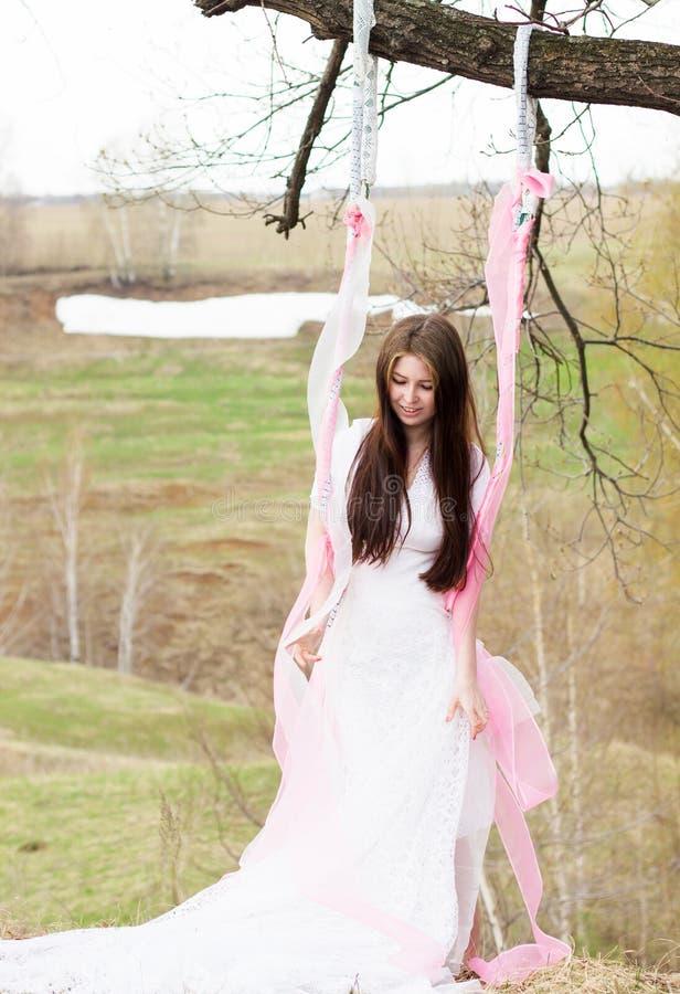 Η όμορφη γυναίκα σε όλο το άσπρο γαμήλιο φόρεμα την ηλιόλουστη ημέρα ταλαντεύεται υπαίθρια στοκ φωτογραφία