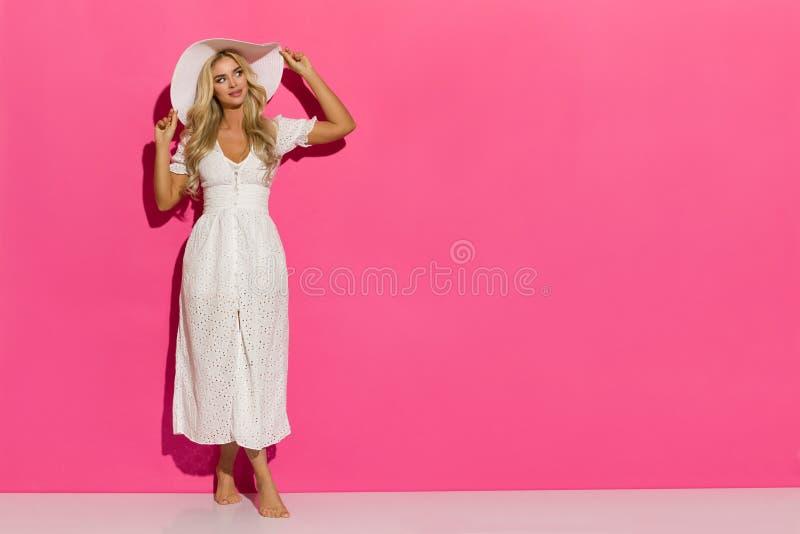 Η όμορφη γυναίκα στο άσπρα θερινό φόρεμα και το καπέλο ήλιων στέκεται ενάντια στο ρόδινο τοίχο στοκ φωτογραφία με δικαίωμα ελεύθερης χρήσης