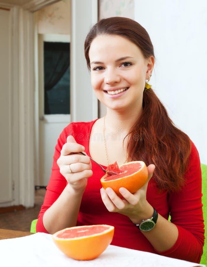 Η όμορφη γυναίκα στο κόκκινο τρώει το γκρέιπφρουτ στοκ εικόνες