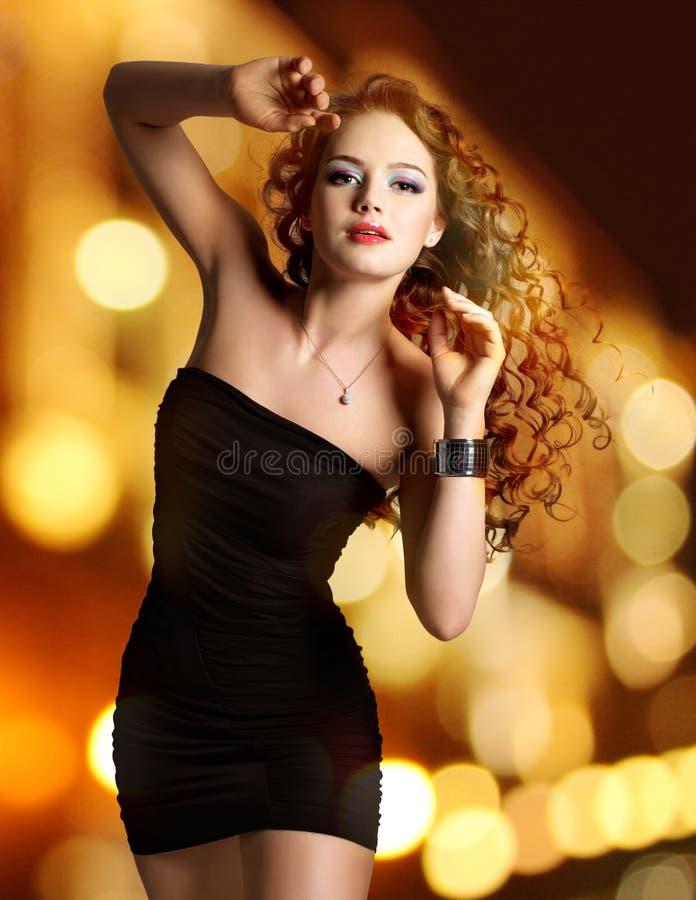 Η όμορφη γυναίκα στο μαύρο φόρεμα θέτει πέρα από τα φω'τα νύχτας στοκ εικόνα με δικαίωμα ελεύθερης χρήσης