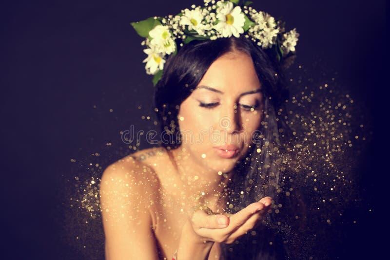 Η όμορφη γυναίκα στο στούντιο με χρυσό ακτινοβολεί στοκ φωτογραφίες