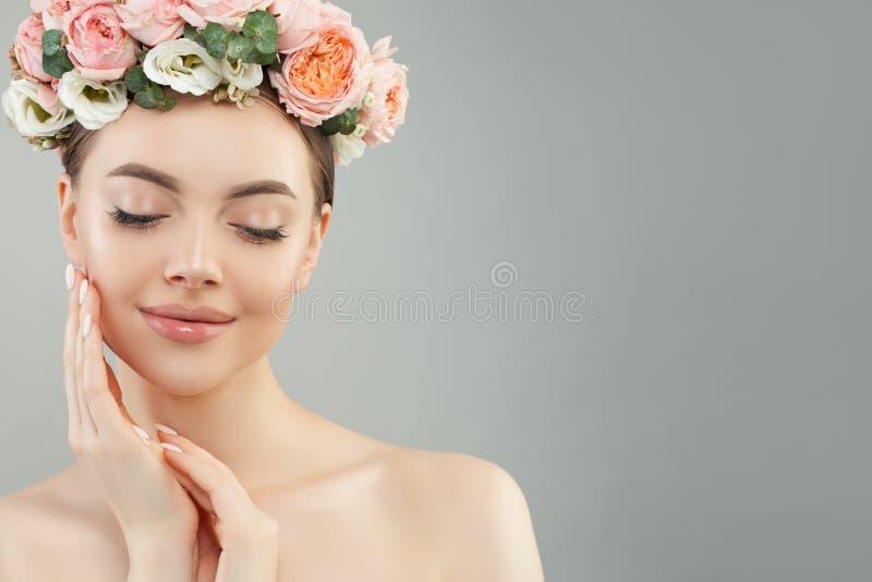 Η όμορφη γυναίκα σχετικά με την αντιμετωπίζει το χέρι της Αρκετά ειλικρινές κορίτσι με τα λουλούδια Του προσώπου επεξεργασία, πρό στοκ εικόνες
