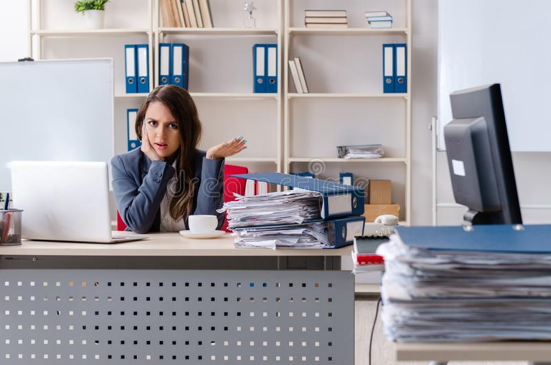 Η όμορφη γυναίκα υπάλληλος δυστυχισμένος με την υπερβολική εργασία στοκ εικόνα