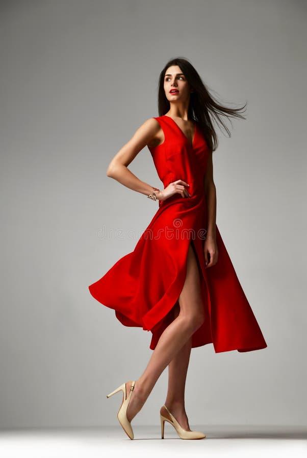 Η όμορφη γυναίκα brunette στο επίσημο κόκκινο στιλέτο φορεμάτων βάζει τακούνια στα παπούτσια στοκ φωτογραφίες με δικαίωμα ελεύθερης χρήσης