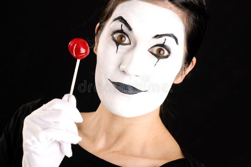 Η όμορφη γυναίκα Mime Brunette κρατά το άσπρο πρόσωπο καραμελών Lollipop στοκ φωτογραφίες