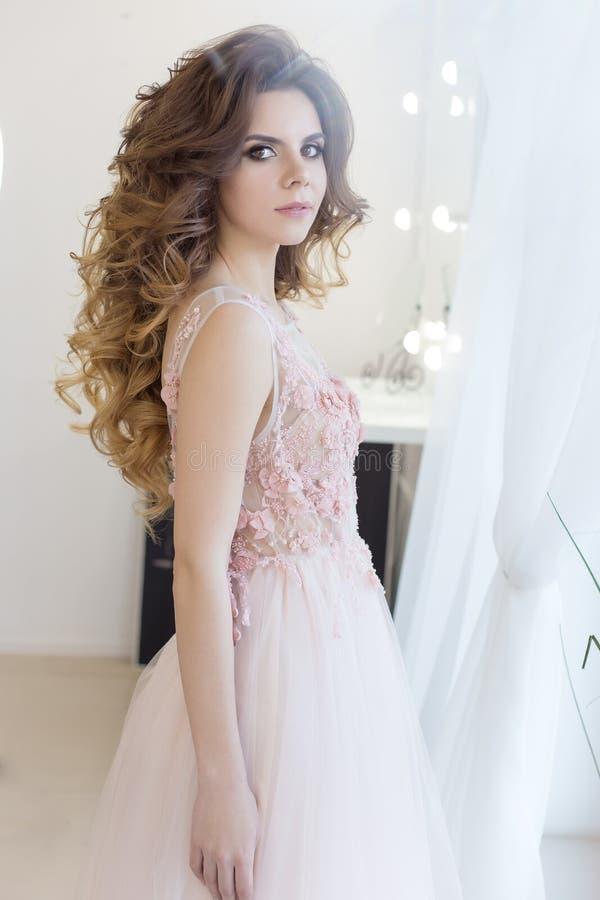 Η όμορφη γλυκιά νύφη κοριτσιών σε ένα γαμήλιο φόρεμα με μεγάλες μπούκλες ενός τις ρόδινες αέρα και το βράδυ ετοιμάζουν, πυροβολισ στοκ εικόνα με δικαίωμα ελεύθερης χρήσης
