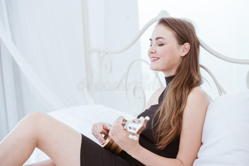 Η όμορφη διασκέδαση κιθάρων παιχνιδιών κοριτσιών απολαμβάνει τον τρόπο ζωής χαλαρώνει τις διακοπές στοκ φωτογραφία με δικαίωμα ελεύθερης χρήσης