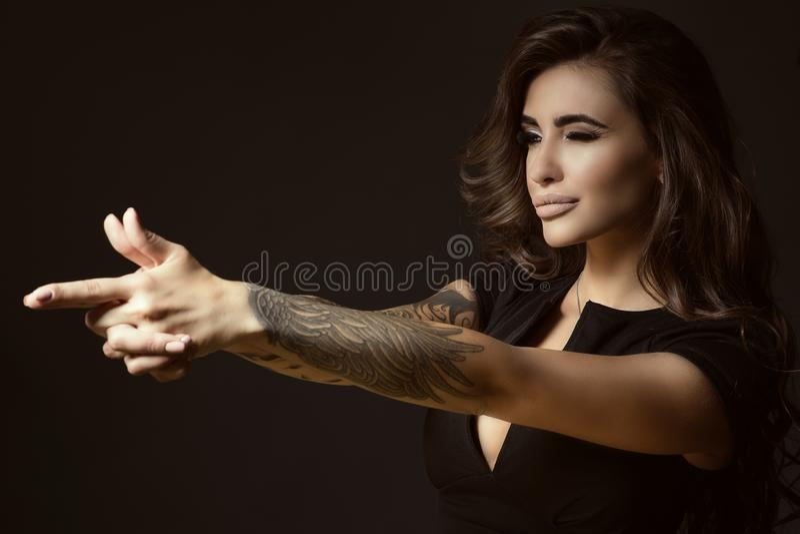 Η όμορφη διαστισμένη γυναίκα με την άφθονη λάμποντας κυματιστή τρίχα και τέλειος αποτελεί την προσποίηση να στοχεύσει κάτι με τη  στοκ εικόνες