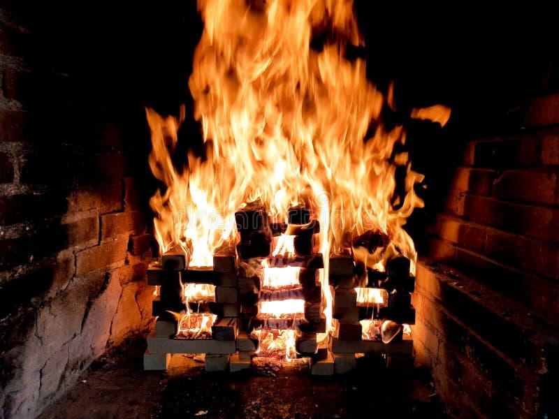 Η όμορφη εικόνα της κίνησης της πυρκαγιάς σε μια φωτιά έκανε με τις ξύλινες σανίδες στο πλέγμα στην εστία τούβλου στοκ φωτογραφία