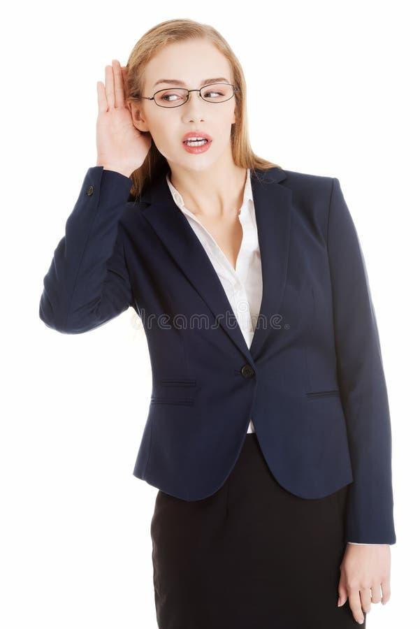 Η όμορφη επιχειρησιακή γυναίκα είναι πέρα να ακούσει, trouching το αυτί της. στοκ εικόνες
