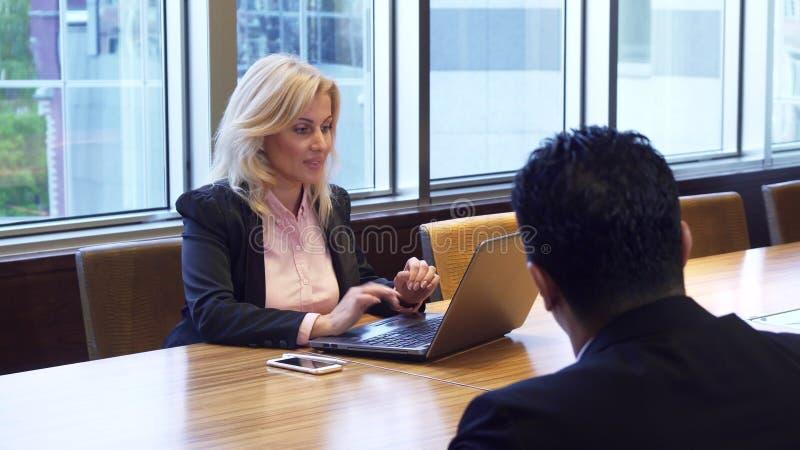 Η όμορφη επιχειρησιακή γυναίκα μιλά καθμένος στον υπολογιστή στοκ φωτογραφίες